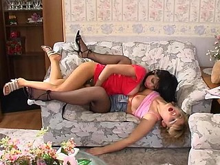 Freaky chicks in soft silky hose having strap-on fucking fun on sofa