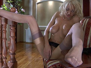 Breasty blond dreamboat flashes her privates whilst putting on her fine nylons