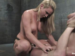 The dominating blonde milf wants the man's cock but she wants to fuck his ass even more! After tieing him with his legs up she sucks his cock and plays with his tight shaved anus before inserting a massive strap on dildo in it. He moans as the dildo goes deep in his rectum and has to obey in front of the busty blonde